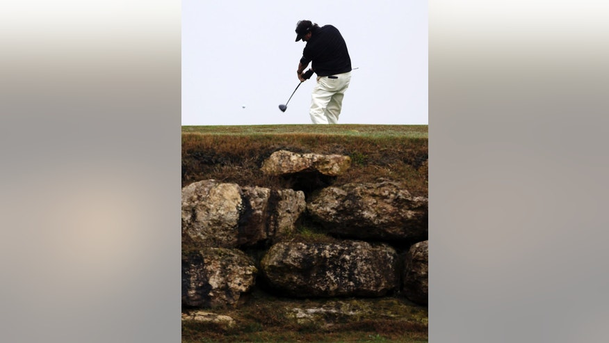 Phil Mickelson hits his tee shot on the 11th hole during the first round of the Valero Texas Open golf tournament, Thursday, March 27, 2014, in San Antonio. Play was delayed for more than two hours Thursday due to rain and fog. (AP Photo/Eric Gay)