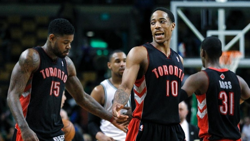 Toronto Raptors guard DeMar DeRozan (10) and forward Amir Johnson (15) congratulate each other as they walk off the court after defeating the Boston Celtics 99-90 in an NBA basketball game in Boston, Wednesday, March 26, 2014. (AP Photo/Elise Amendola)