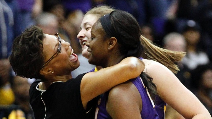 LSU basketball coach Nikki Caldwell, left, hugs LSU forwards Shanece McKinney, right and Theresa Plaisance as they leave the court in the final seconds of their NCAA college basketball second-round tournament game against West Virginia, Tuesday, March 25, 2014, in Baton Rouge, La. LSU won 76-67. (AP Photo/Rogelio V. Solis)