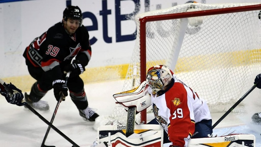 Florida Panthers goalie Dan Ellis (39) is unable to block Carolina Hurricanes' Patrick Dwyer (39) who assists on the Hurricanes' third goal during the second period of an NHL hockey game in Sunrise, Fla., Thursday, March 27, 2014. (AP Photo/J Pat Carter)