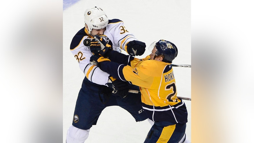 Buffalo Sabres left wing John Scott (32) collides with Nashville Predators forward Patric Hornqvist (27), of Sweden, while attempting to get control of the puck in the second period of an NHL hockey game on Thursday, March 27, 2014, in Nashville, Tenn.  (AP Photo/Mark Zaleski)