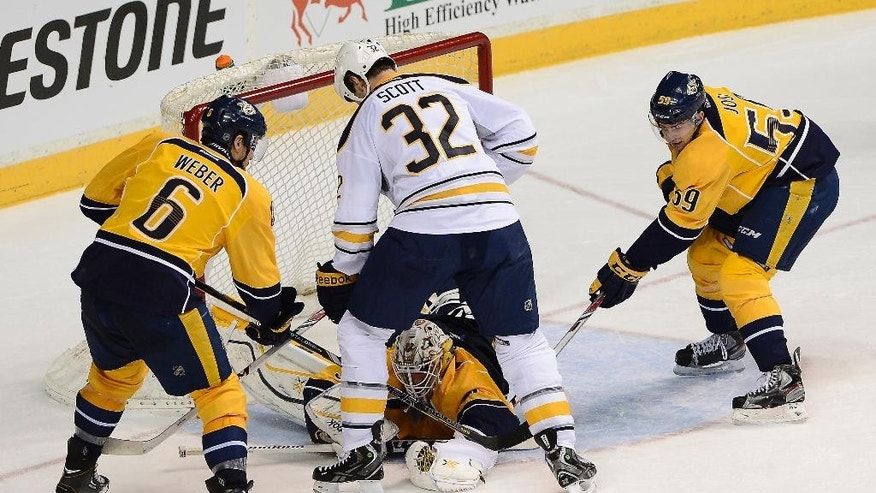 Nashville Predators goalie Carter Hutton, bottom center, covers up the puck after a shot by Buffalo Sabres left wing John Scott (32) in the third period of an NHL hockey game on Thursday, March 27, 2014, in Nashville, Tenn. Predators' Shea Weber (6) and Roman Josi (59), of Switzerland, also defend. (AP Photo/Mark Zaleski)