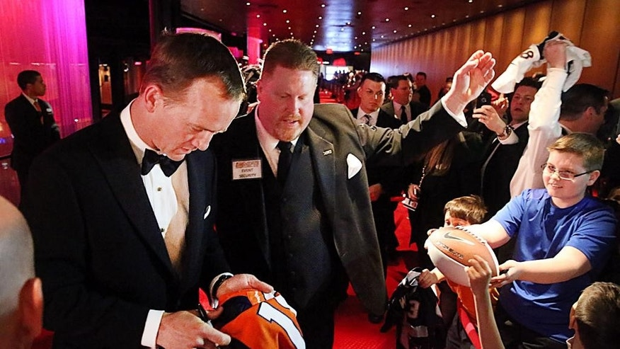 FILE - Denver Broncos quarterback Peyton Manning, left, signs autographs while walking the red carpet to the Ovation Theater, in this March 14 2014 file photo taken at the Maxwell Football Awards at the Revel Casino and Hotel in Atlantic City, N.J. (AP Photo/The Press of Atlantic City, Ben Fogletto) MANDATORY CREDIT