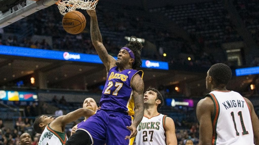 Los Angeles Lakers' Jordan Hill dunks as the Milwaukee Bucks defenders look on during the first half of an NBA basketball game Thursday, March 27, 2014, in Milwaukee. (AP Photo/Tom Lynn)
