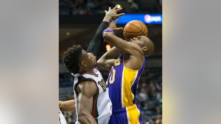 Milwaukee Bucks' Jeff Adrien can not stop Los Angeles Lakers' Jodie Meeks on a drive to the basket during the first half of an NBA basketball game Thursday, March 27, 2014, in Milwaukee. (AP Photo/Tom Lynn)