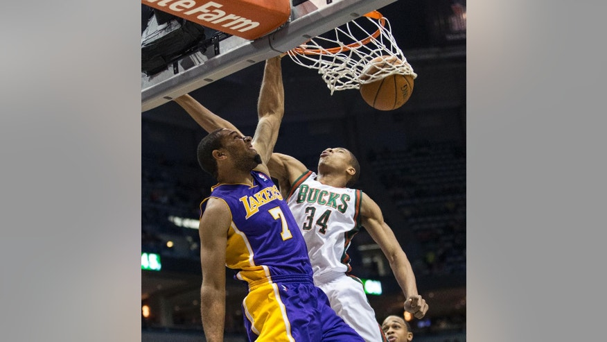 Milwaukee Bucks' Giannis Antetokounmpo can not stop Los Angeles Lakers' Xavier Henry from dunking the ball during the first half of an NBA basketball game Thursday, March 27, 2014, in Milwaukee. (AP Photo/Tom Lynn)