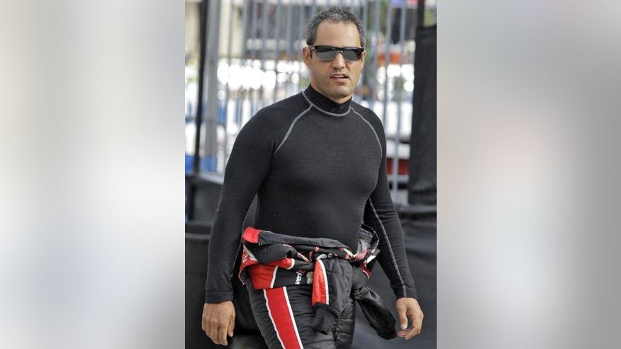 Juan Pablo Montoya, of Colombia, walks to his car before practice for the IndyCar Firestone Grand Prix of St. Petersburg auto race Friday, March 28, 2014, in St. Petersburg, Fla. The race takes place on Sunday. (AP Photo/Chris O'Meara)