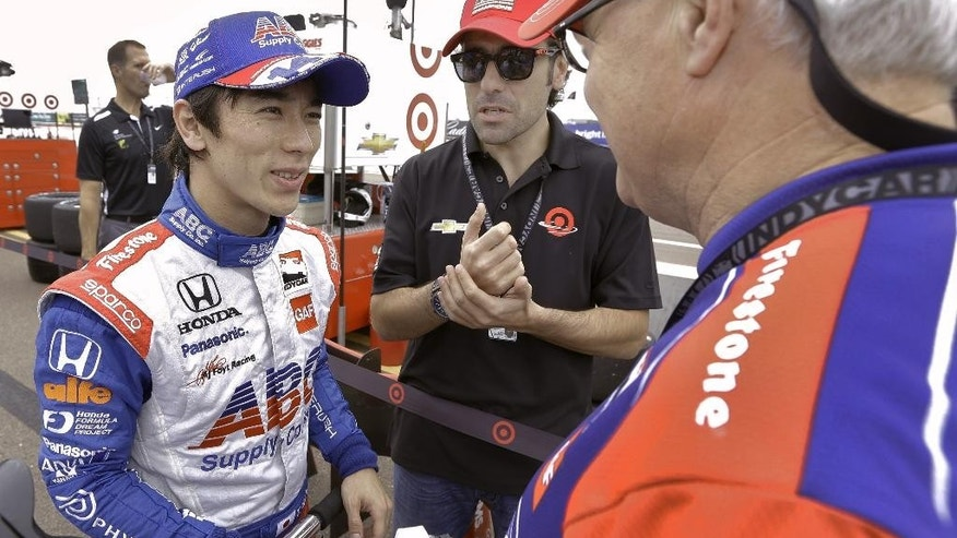 Driver Takuma Sato, of Japan, left, talks to chief engineer Don Halliday, right, and Ganassi driving coach Dario Franchitti, of Scotland, during practice for the IndyCar Firestone Grand Prix of St. Petersburg auto race Friday, March 28, 2014, in St. Petersburg, Fla. The race takes place on Sunday. (AP Photo/Chris O'Meara)