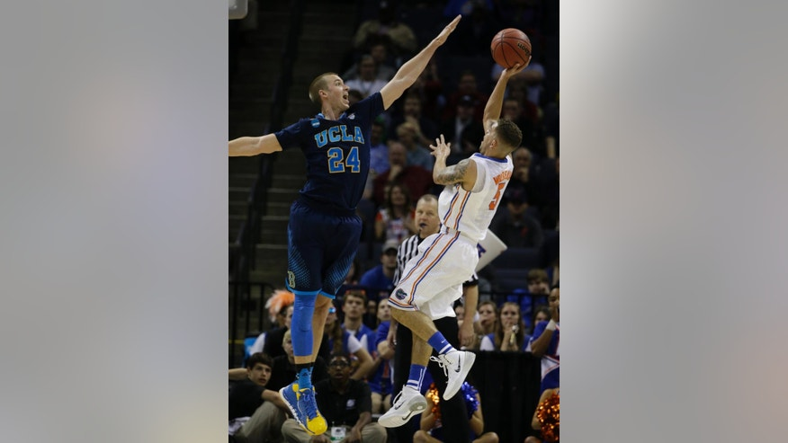 Florida guard Scottie Wilbekin (5) shoots against UCLA forward Travis Wear (24) during the second half in a regional semifinal game at the NCAA college basketball tournament, Thursday, March 27, 2014, in Memphis, Tenn. Florida won 79-68. (AP Photo/Mark Humphrey)
