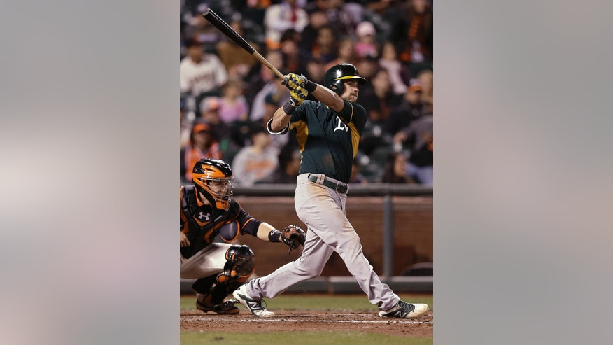 Oakland Athletics' Josh Reddick follows through on a two-run home run off San Francisco Giants pitcher Tim Hudson during the sixth inning of an exhibition baseball game in San Francisco, Thursday, March 27, 2014. At left is Giants catcher Buster Posey. (AP Photo/Jeff Chiu)