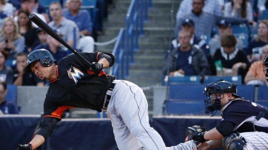 Miami Marlins' Giancarlo Stanton loses his footing and falls to the dirt in the first inning of a spring exhibition baseball game against the New York Yankees in Tampa, Fla., Friday, March 28, 2014. The Yankees defeated the Marlins 3-0. (AP Photo/Kathy Willens)