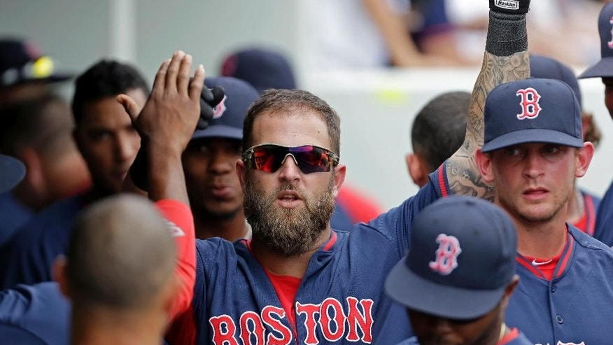 Boston Red Sox' Mike Napoli celebrates in the dugout after his solo homer in the sixth inning of an exhibition baseball game against the Minnesota Twins in Fort Myers, Fla., Friday, March 28, 2014. (AP Photo/Gerald Herbert)