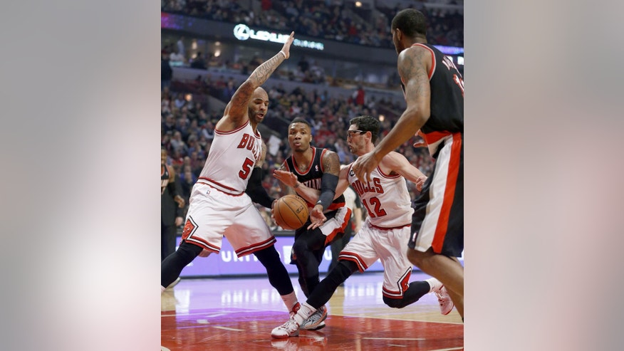Portland Trail Blazers guard Damian Lillard, center, passes the ball to LaMarcus Aldridge, right as Chicago Bulls forward Carlos Boozer (5) and Kirk Hinrich (12) defend during the first half of an NBA basketball game Friday, March 28, 2014, in Chicago. (AP Photo/Charles Rex Arbogast)