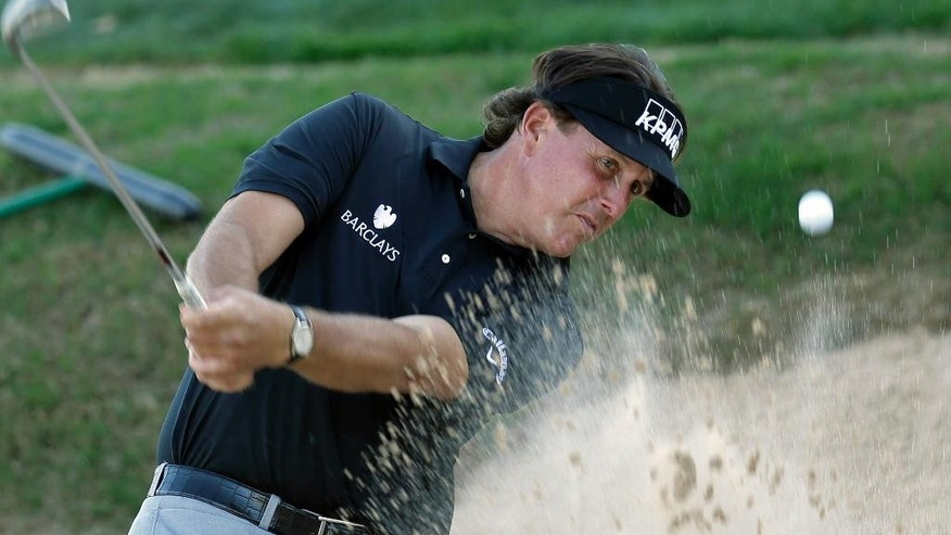 Phil Mickelson blasts from a sand trap on the 16th hole during the second round of the Texas Open golf tournament on Friday, March 28, 2014, in San Antonio. (AP Photo/Eric Gay)