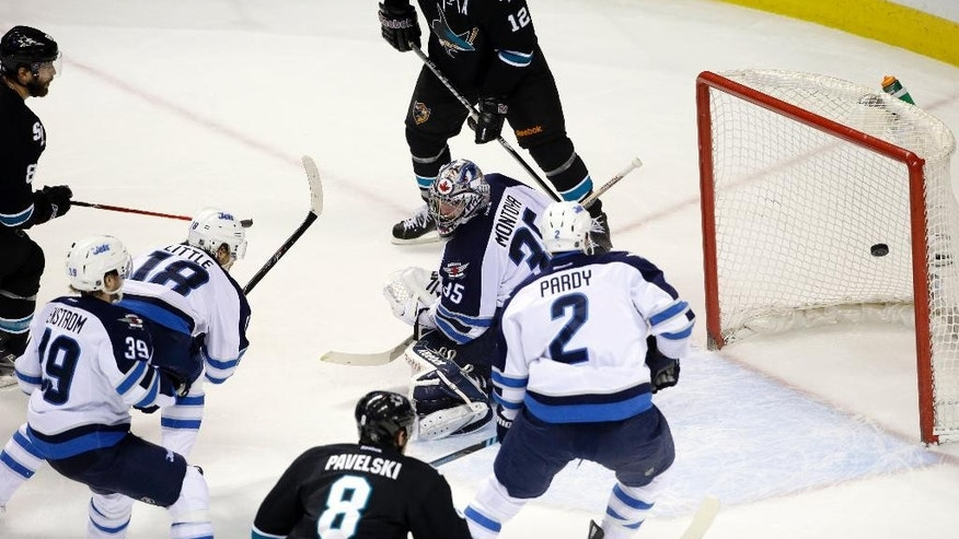 San Jose Sharks' Brent Burns, left, scores past Winnipeg Jets goalie Al Montoya, center, during the first period of an NHL hockey game Thursday, March 27, 2014, in San Jose, Calif. (AP Photo/Marcio Jose Sanchez)