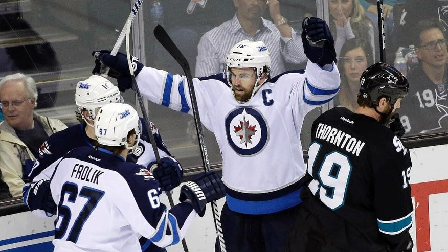 Winnipeg Jets' Andrew Ladd, center, celebrates his goal against the San Jose Sharks during the first period of an NHL hockey game Thursday, March 27, 2014, in San Jose, Calif. (AP Photo/Marcio Jose Sanchez)