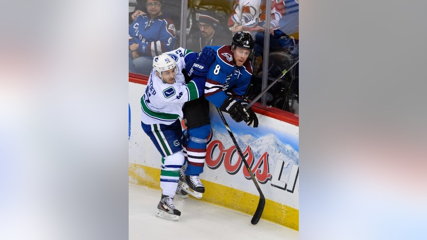 Vancouver Canucks center Jordan Schroeder (45) checks Colorado Avalanche defenseman Jan Hejda (8), from the Czech Republic, into the boards during the first period of an NHL hockey game on Thursday, March 27, 2014, in Denver. (AP Photo/Jack Dempsey)