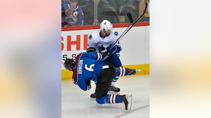 Vancouver Canucks left wing Chris Higgins (20) knocks Colorado Avalanche defenseman Erik Johnson (6) off his skates during the first period of an NHL hockey game on Thursday, March 27, 2014, in Denver. (AP Photo/Jack Dempsey)