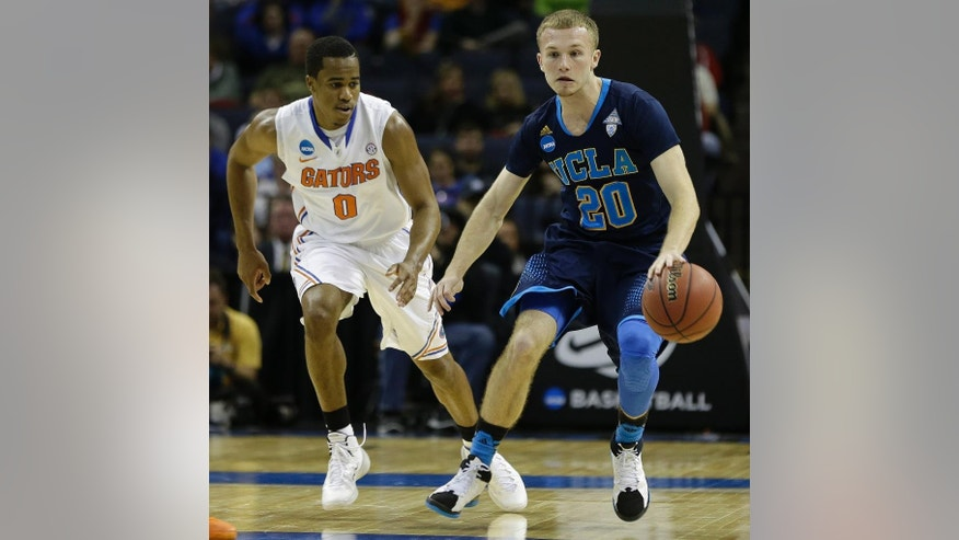 UCLA guard Bryce Alford (20) moves the ball against Florida's Kasey Hill during the second half in a regional semifinal game at the NCAA college basketball tournament, Thursday, March 27, 2014, in Memphis, Tenn. (AP Photo/Mark Humphrey)