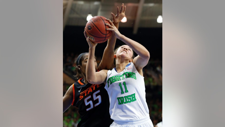 Notre Dame forward Natalie Achonwa (11) is fouled by Oklahoma State center LaShawn Jones (55) during the first half of a regional semifinal in the NCAA college basketball tournament at the Purcell Pavilion in South Bend, Ind., Saturday, March 29, 2014. (AP Photo/Paul Sancya)