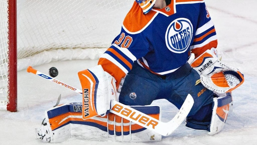 Edmonton Oilers' Ben Scrivens (30) makes a save against the Anaheim Ducks during second-period NHL hockey game action in Edmonton, Alberta, Friday, March 28, 2014. (AP Photo/The Canadian Press, Jason Franson)