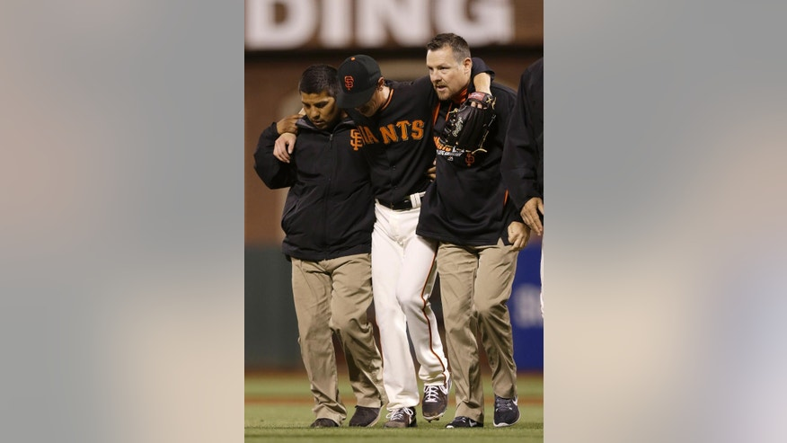 San Francisco Giants pitcher Tim Lincecum, center, is helped off the field by trainers after being struck by a ball hit by Oakland Athletics' Daric Barton during the fourth inning of an exhibition baseball game in San Francisco, Friday, March 28, 2014. (AP Photo/Jeff Chiu)