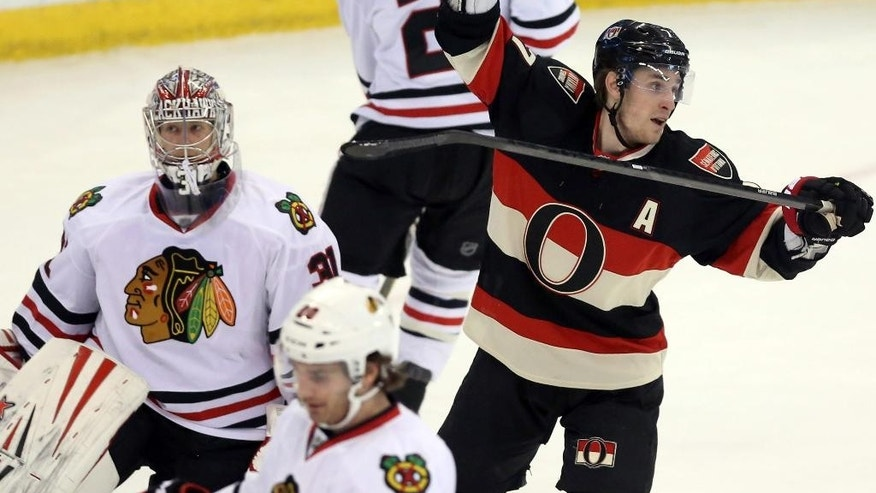 Ottawa Senators' Kyle Turris (7) celebrates a goal by teammate Cory Ceci as Chicago Blackhawks goaltender Antti Raanta, left, of Finland, looks on during first-period NHL hockey game action in Ottawa, Ontario, Friday, March 28, 2014. (AP Photo/The Canadian Press, Fred Chartrand)