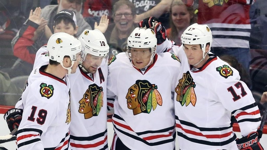 Chicago Blackhawks' Marian Hossa (81) celebrates his goal with teammates Jonathan Toews (19), Patrick Sharp (10) and Sheldon Brookbank (17) during second-period NHL hockey game action against the Ottawa Senators in Ottawa, Ontario, Friday, March 28, 2014. (AP Photo/The Canadian Press, Fred Chartrand)