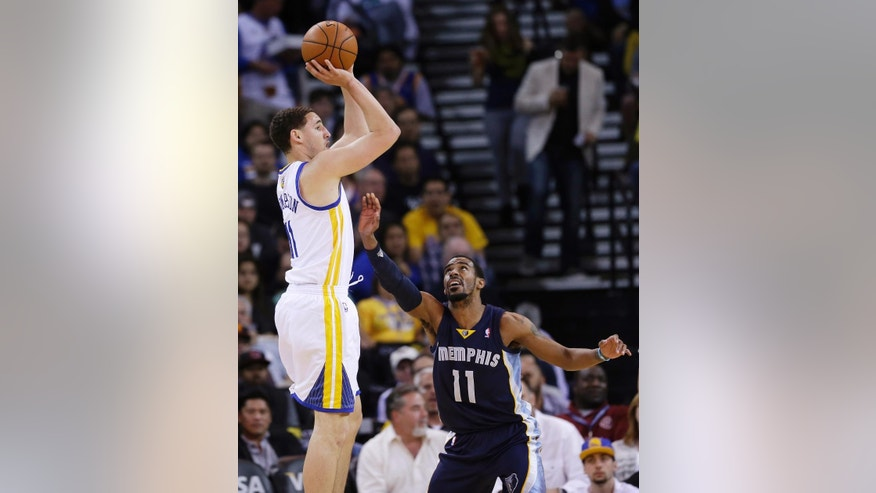Golden State Warriors guard Klay Thompson shoots over Memphis Grizzlies guard Mike Conley (11) during the first half of an NBA basketball game Friday, March 28, 2014, in Oakland, Calif. (AP Photo/Marcio Jose Sanchez)