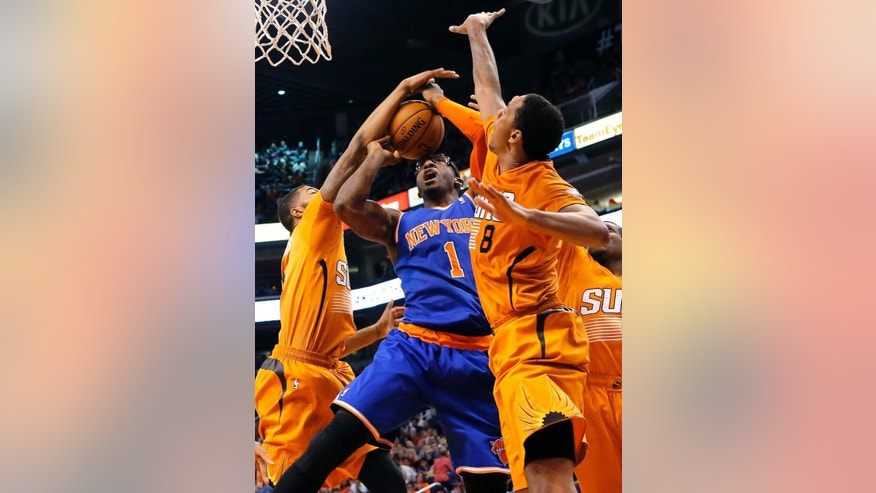 New York Knicks' Amare Stoudemire (1) has his shot blocked by Phoenix Suns' Markeiff Morris, left, and Channing Frye (8) during the first half of an NBA basketball game, Friday, March 28, 2014, in Phoenix. (AP Photo/Matt York)
