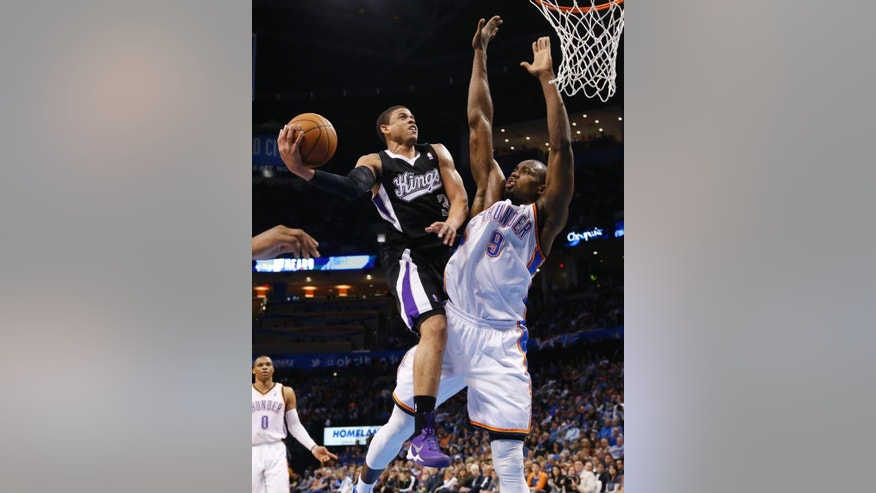 Sacramento Kings guard Ray McCallum (3) goes up for a shot in front of Oklahoma City Thunder forward Serge Ibaka (9) during the second quarter of an NBA basketball game in Oklahoma City, Friday, March 28, 2014. (AP Photo/Sue Ogrocki)
