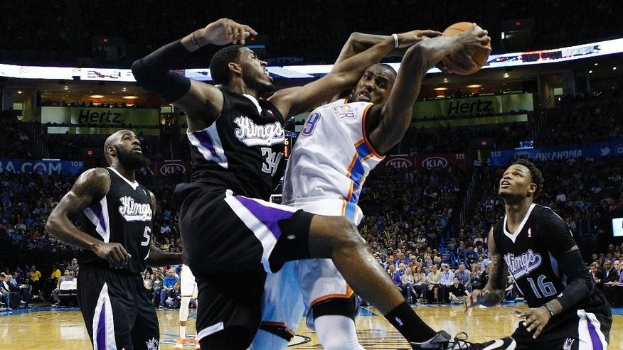 Oklahoma City Thunder forward Serge Ibaka (9) is fouled by Sacramento Kings forward Jason Thompson (34) during the second quarter of an NBA basketball game in Oklahoma City, Friday, March 28, 2014. (AP Photo/Sue Ogrocki)