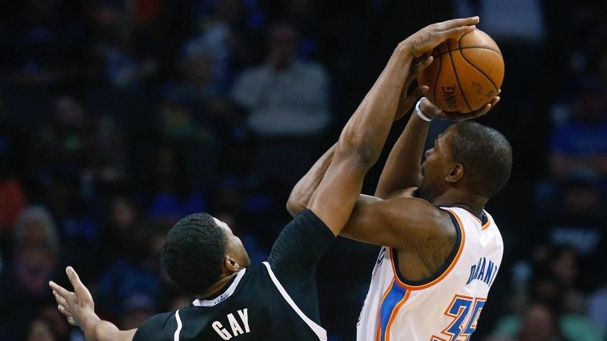 Oklahoma City Thunder forward Kevin Durant (35) is fouled by Sacramento Kings forward Rudy Gay (8) duringthe first quarter of an NBA basketball game in Oklahoma City, Friday, March 28, 2014. (AP Photo/Sue Ogrocki)