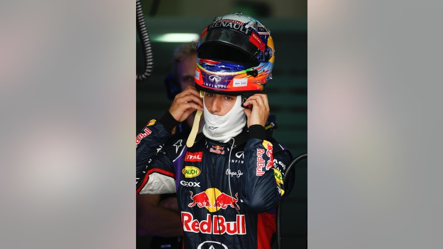 Red Bull Racing driver Daniel Ricciardo of Australia put on his helmet before the third practice session for the Malaysian Formula One Grand Prix at Sepang International Circuit in Sepang, Malaysia, Saturday, March 29, 2014. (AP Photo/Vincent Thian)