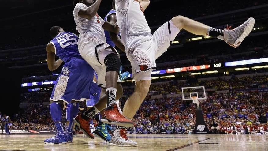 Louisville's Stephan Van Treese grabs a rebound during the first half of an NCAA Midwest Regional semifinal college basketball tournament game against the Kentucky Friday, March 28, 2014, in Indianapolis. (AP Photo/David J. Phillip)