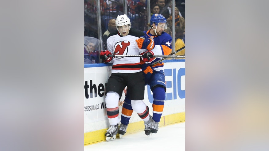 New Jersey Devils left wing Tuomo Ruutu (15) and New York Islanders defenseman Calvin de Haan (44) collide in the first period of an NHL hockey game on Saturday, March 29, 2014, in Uniondale, N.Y. (AP Photo/John Minchillo)