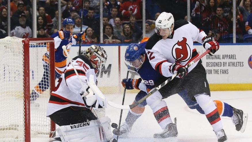 New Jersey Devils goalie Cory Schneider (35) makes a save against New York Islanders center Brock Nelson (29) as Devils right wing Damien Brunner (12) defends in the second period of an NHL hockey game on Saturday, March 29, 2014, in Uniondale, N.Y. (AP Photo/John Minchillo)