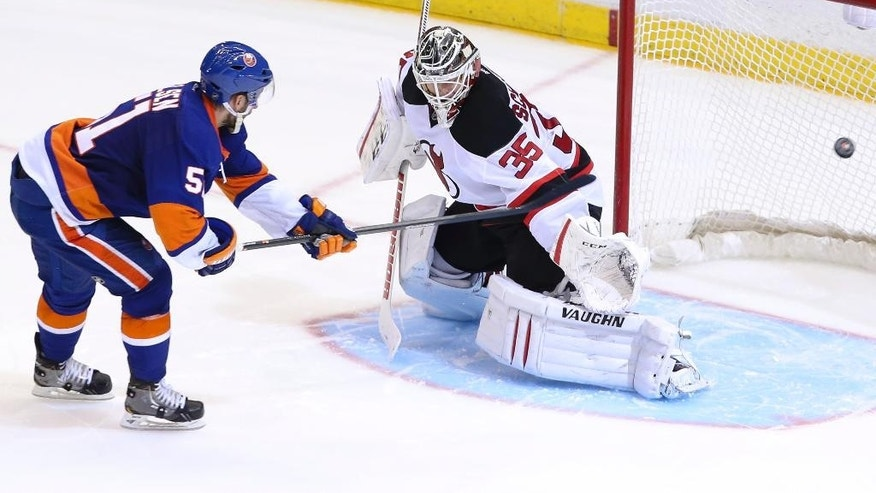 New York Islanders center Frans Nielsen (51) scores against New Jersey Devils goalie Cory Schneider (35) during a shootout of an NHL hockey game on Saturday, March 29, 2014, in Uniondale, N.Y. The Islanders defeated the Devils 2-1. (AP Photo/John Minchillo)