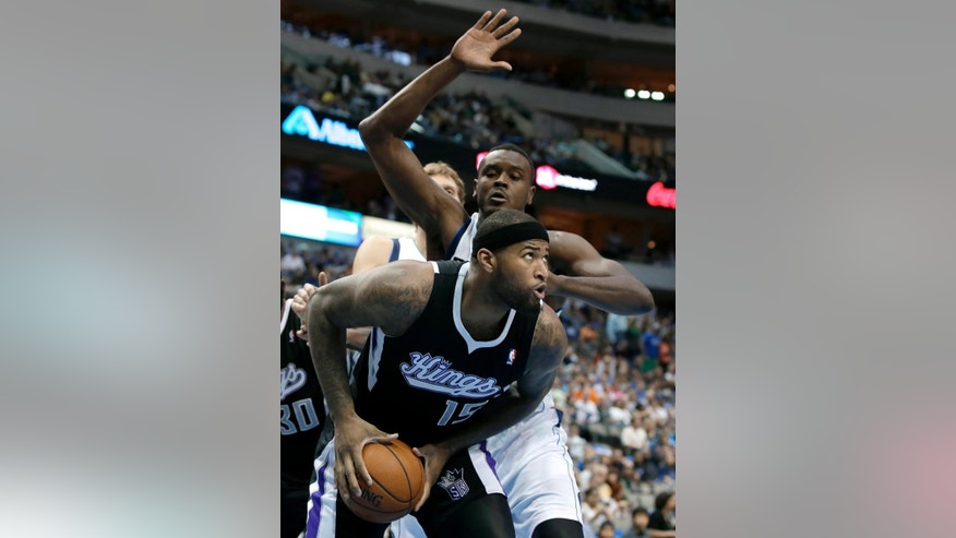 Sacramento Kings' DeMarcus Cousins (15) looks to the basket before going up for a shot as Dallas Mavericks' Samuel Dalembert, rear, of Haiti, defends in the first half of an NBA basketball game, Saturday, March 29, 2014, in Dallas. (AP Photo/Tony Gutierrez)