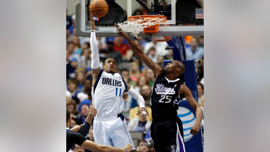 Dallas Mavericks' Monta Ellis (11) goes up for a reverse layup as Sacramento Kings' Travis Outlaw (25) defends in the first half of an NBA basketball game, Saturday, March 29, 2014, in Dallas. (AP Photo/Tony Gutierrez)