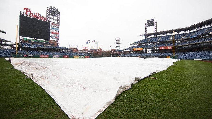 The tarp covers the field as the exhibition baseball game between the Pittsburgh Pirates and the Philadelphia Phillies is canceled due to rain, Saturday, March 29, 2014, in Philadelphia. (AP Photo/Chris Szagola)