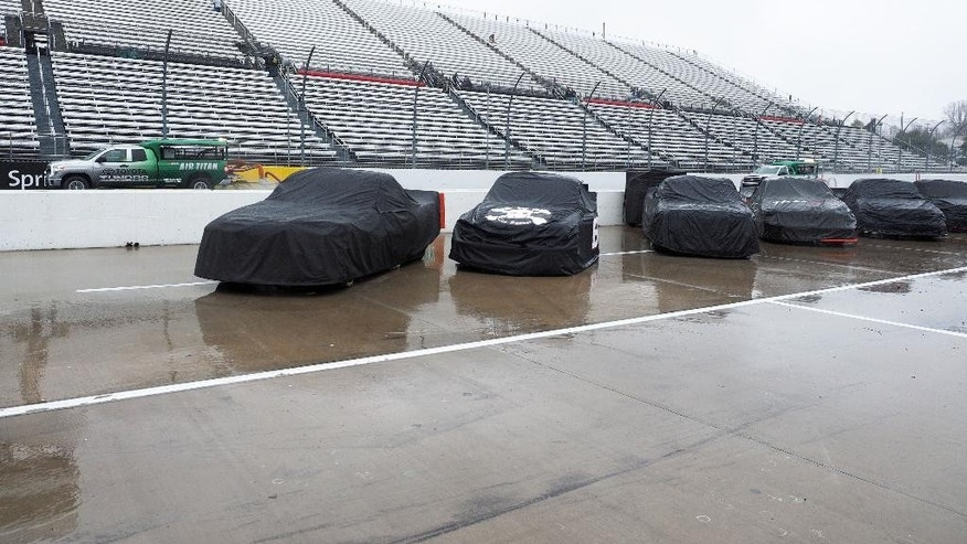 Trucks sit under covers as Air Titans try to keep the track dry during a rain delay at the  NASCAR Truck Series auto race at Martinsville Speedway in Martinsville, Va., Saturday, March 29, 2014. (AP Photo/Steve Sheppard)