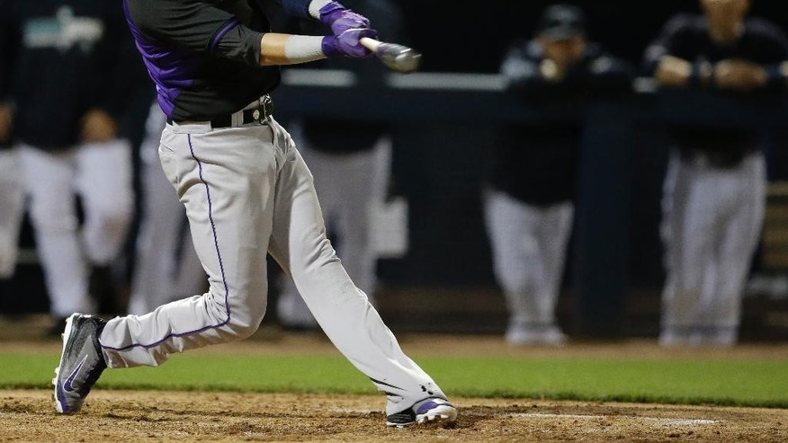 Colorado Rockies' Troy Tulowitzki hits an RBI double during the third inning of a spring exhibition baseball game against the Seattle Mariners on Friday, March 28, 2014, in Peoria, Ariz. Corey Dickerson scored. (AP Photo/Darron Cummings)