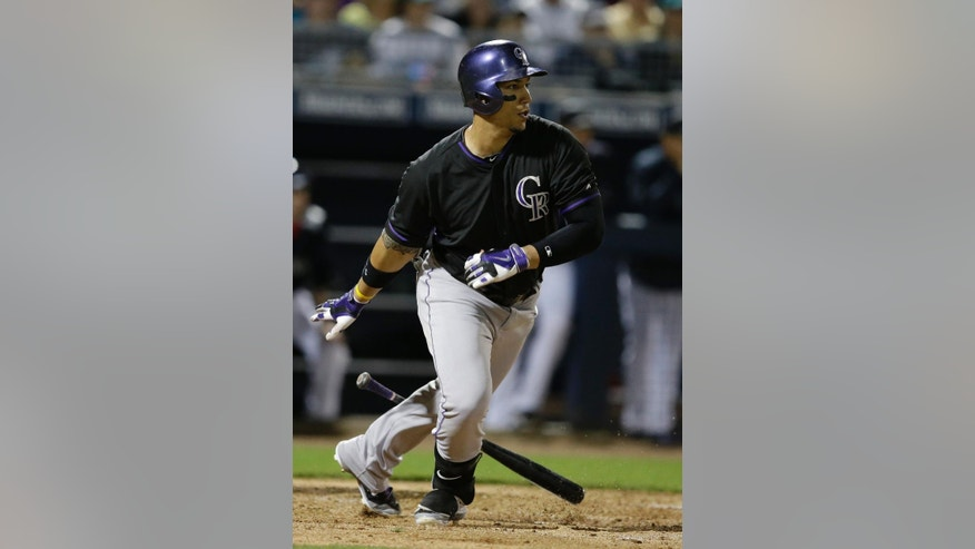 Colorado Rockies' Carlos Gonzalez watches his RBI single during the third inning of an exhibition baseball game against the Seattle Mariners on Friday, March 28, 2014, in Peoria, Ariz. Troy Tulowitzki scored. (AP Photo/Darron Cummings)