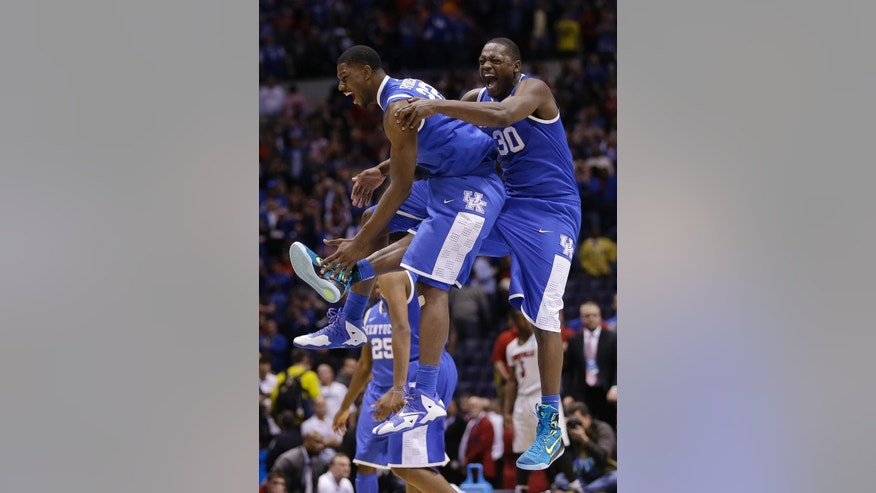 Kentucky's Alex Poythress and Aaron Harrison celebrate after an NCAA Midwest Regional semifinal college basketball tournament game against the Louisville Saturday, March 29, 2014, in Indianapolis. Kentucky won 74-69. (AP Photo/David J. Phillip)