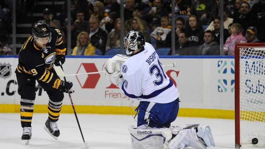 Buffalo Sabres center Cody Hodgson (19) scores on Tampa Bay Lightning goaltender Ben Bishop (30) during the first period of an NHL hockey game in Buffalo, N.Y., Saturday, March 29, 2014. (AP Photo/Gary Wiepert)