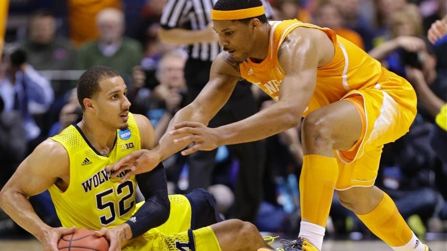 Michigan's Jordan Morgan and Tennessee's Jarnell Stokes go after a loose ball during the first half of an NCAA Midwest Regional semifinal college basketball tournament game Friday, March 28, 2014, in Indianapolis. (AP Photo/Michael Conroy)