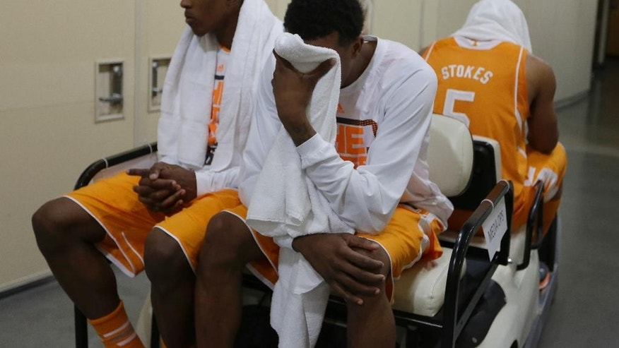 Tennessee guard Josh Richardson, left, and Jordan McRae look down in the cart as they head to the locker room after an NCAA Midwest Regional semifinal college basketball tournament game Friday, March 28, 2014, in Indianapolis. Michigan won 73-71. (AP Photo/Michael Conroy)