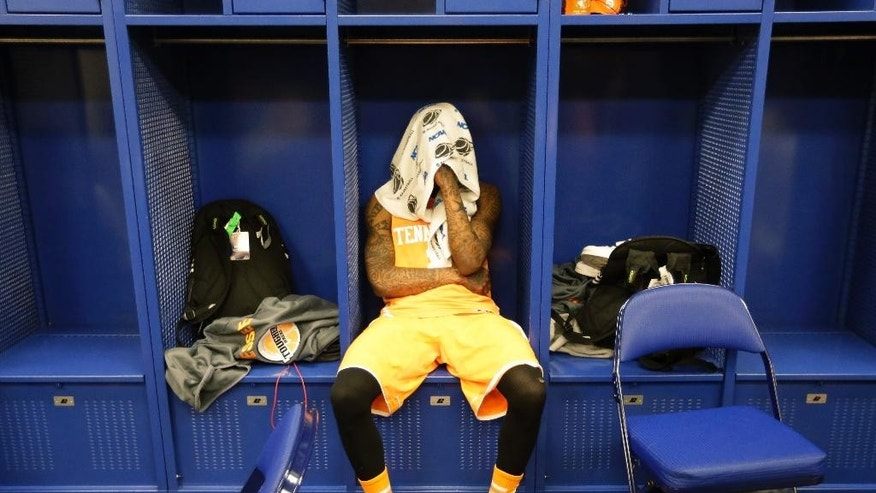 Tennessee guard Antonio Barton (2) looks down in the locker room after an NCAA Midwest Regional semifinal college basketball tournament game Friday, March 28, 2014, in Indianapolis. Michigan won 73-71. (AP Photo/Michael Conroy)