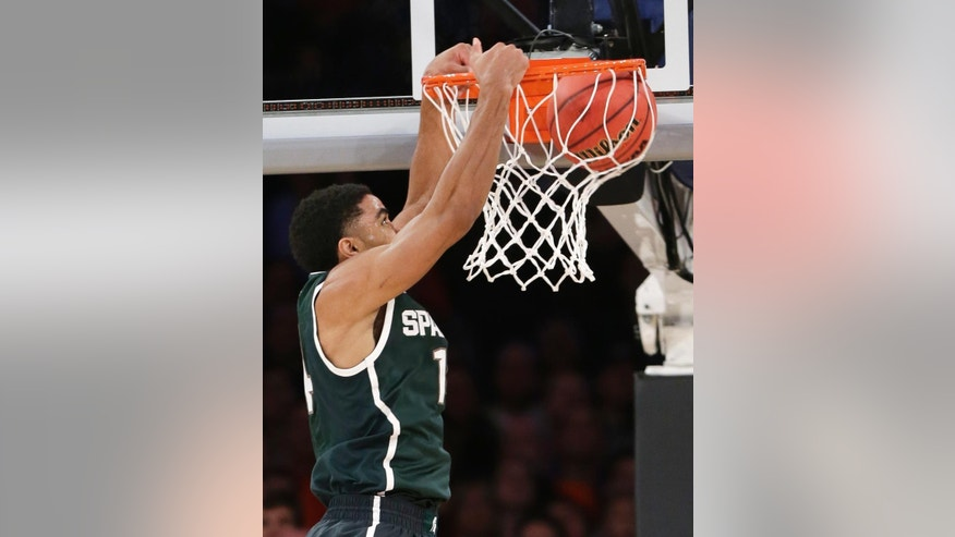 Michigan State's Gary Harris dunks during the first half of a regional semifinal against Virginia at the NCAA men's college basketball tournament, Friday, March 28, 2014, in New York. (AP Photo/Frank Franklin II)